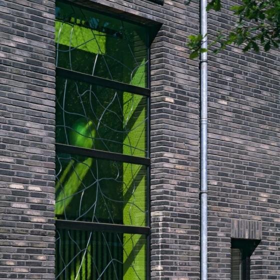 Handgefertigtes Glas  Blickfang sind hier die grünen bleiverglasten Treppenhausfenster. Foto © Werner Huthmacher