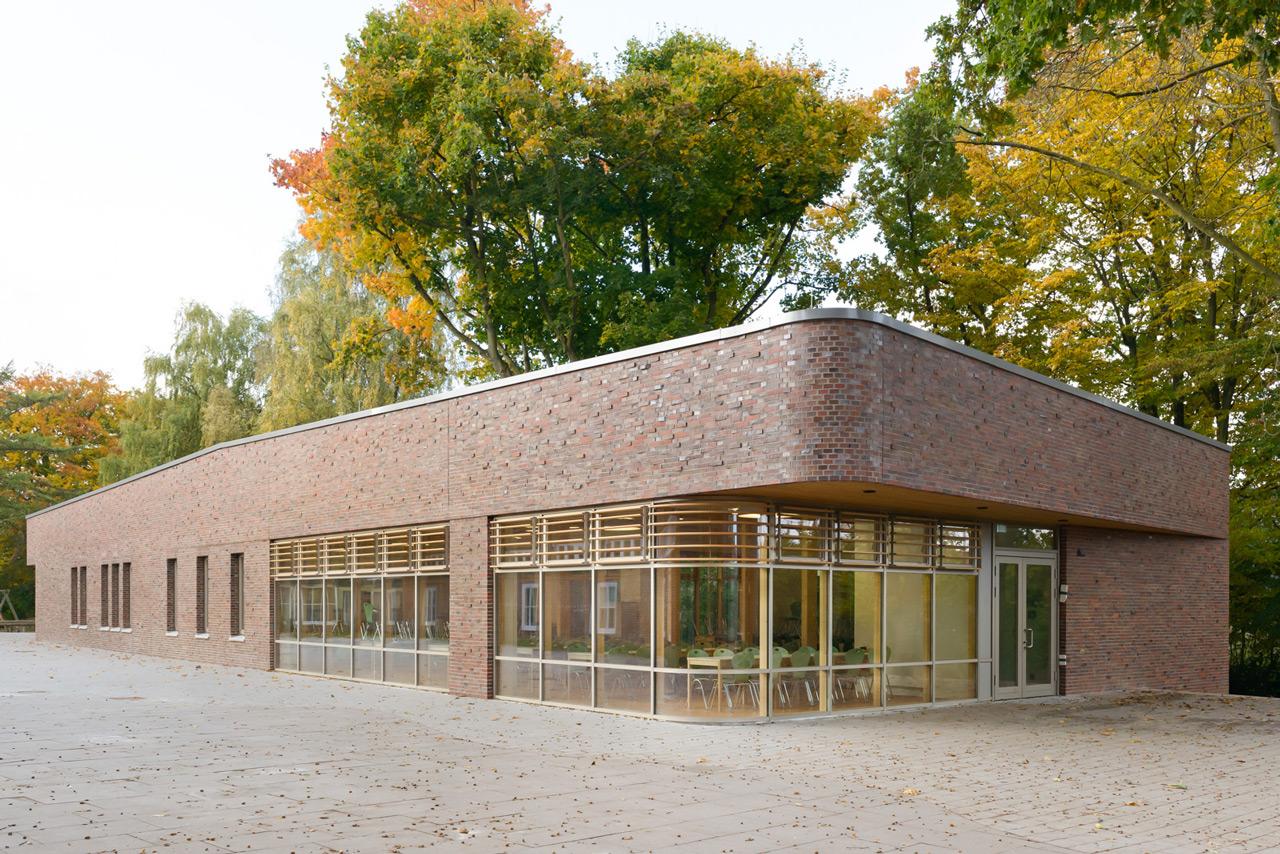 Ein Gebäudeunterschnitt betont den Eingangsbereich, der hierdurch gleichzeitig vor Witterung geschützt wird. Die mehrfarbigen, unregelmäßigen Klinker der Vorhangfassade erzeugen ein lebendiges Fassadenbild. Foto © Kay Riechers
