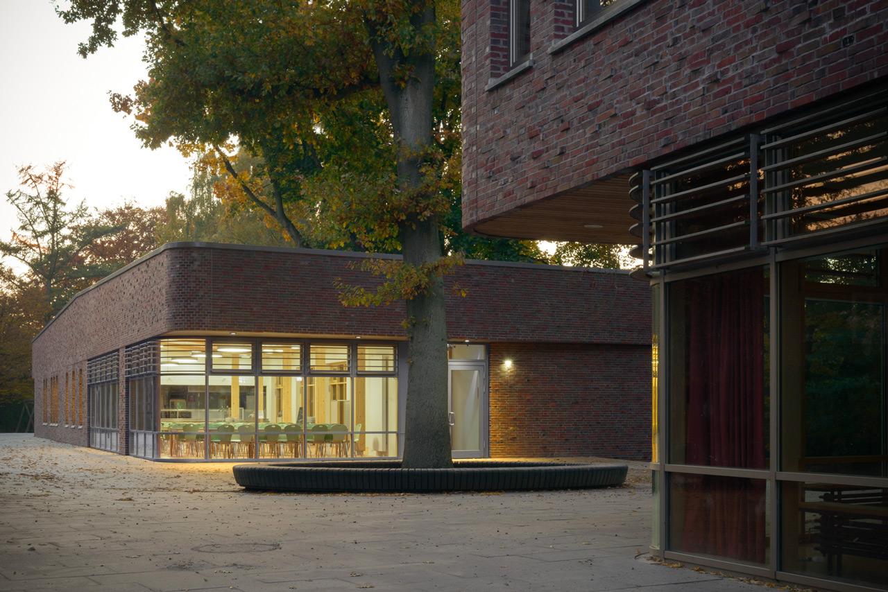 Der eingeschossige Mensaneubau nimmt die Architektursprache und Materialität des benachbarten Klassengebäudes (im Vordergrund) auf. Foto © Kay Riechers